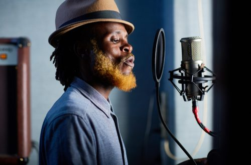 Young bearded man in hat singing in recording studio